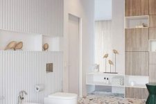 a creative bathroom with white walls and a bright terrazzo floor, white appliances and a plywood storage unit plus pendant lamps