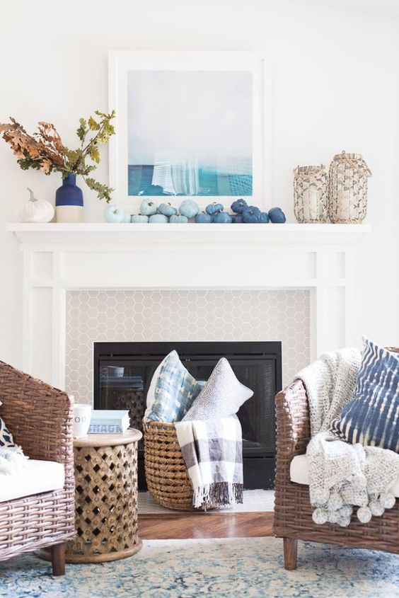 a creative coastal fall mantel with blue pumpkins featuring an ombre effect, with a color  block vase with fall leaves and candle lanterns in woven rope