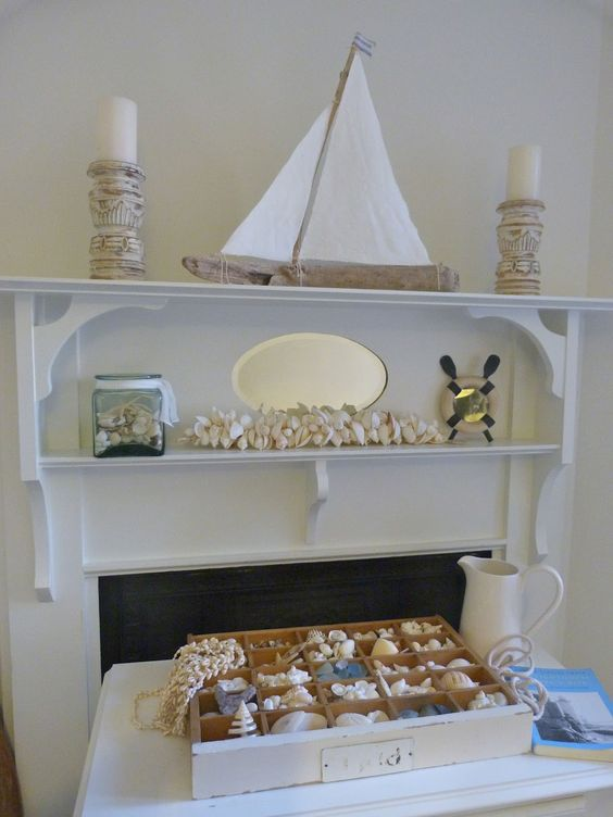 a creative coastal mantel with seashells, a boat, carved wooden candle holders and a jar with seashells is very cool