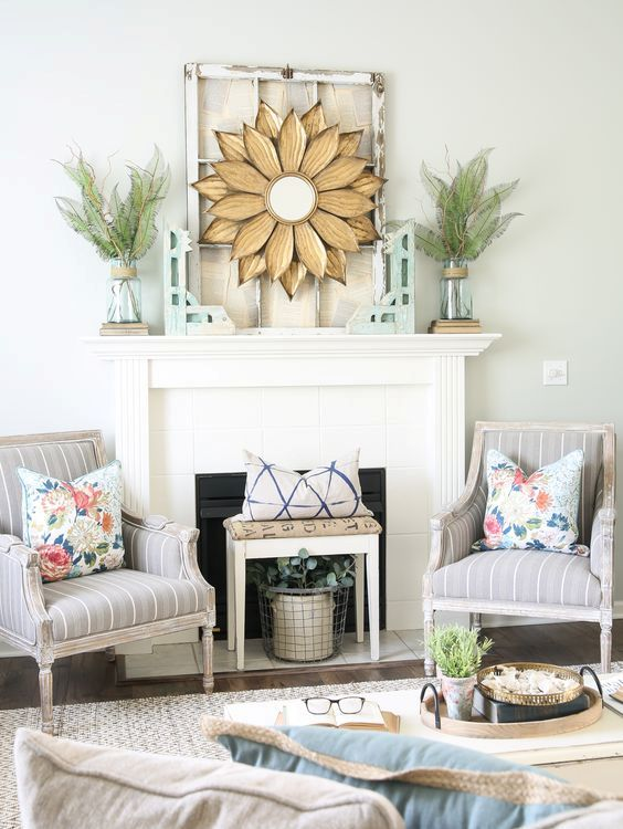 a creative summer mantel with fern and twig arrangements in a vase, a sunburst mirror, a vintage window frame