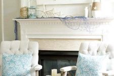 a cute rustic coastal mantel with a driftwood crab artwork, starfish, blue net, vases wrapped with rope and a candle lantern