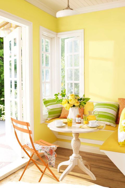 a cute rustic dining space with lemon yellow walls, a built-in yellow bench, an orange chair and colorful printed pillows