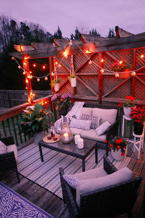 a deck with dark woven furniture, potted blooms, string lights over the space and printed pillows is cozy and welcoming