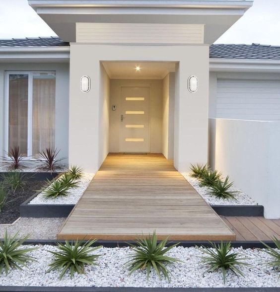 a delicate front yard with white pebbles, succulents and dark succulents, with a deck that leads to the entrance is a very chic and laconic space