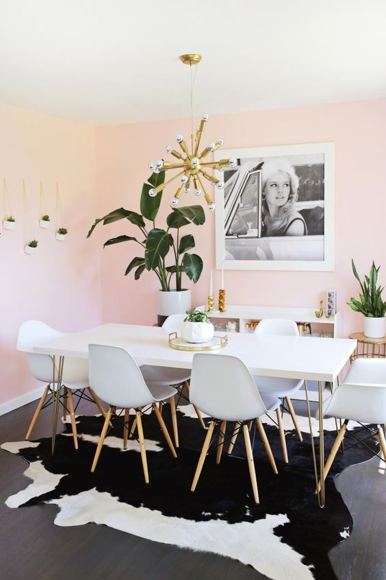 a dreamy dining space with light pink walls, a hairpin leg table and white chairs, potted plants and a gold sunburst chandelier