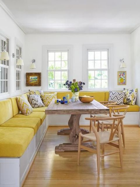a farmhouse dining room with a built-in bench, a wooden dining table, wooden chairs, colorful printed pillows
