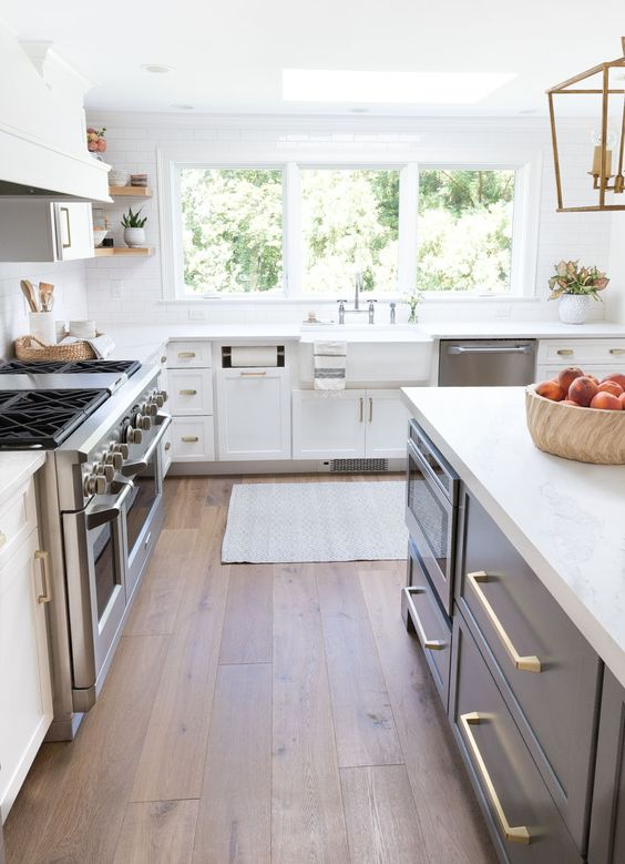 a farmhouse kitchen with hardwood floors, white cabinets and a navy kitchen island, gold touches and pendant lamps