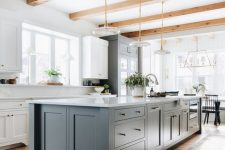 a farmhouse kitchen with white cabinets and a slate grey ktichen island, wooden beams and lovely plate pendant lamps plus wooden beams