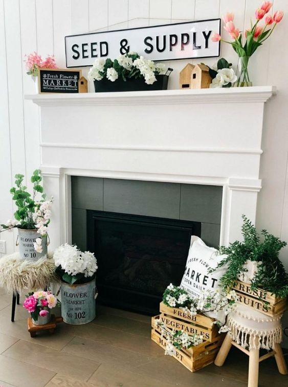a farmhouse summer mantel with pink and white blooms, greenery, a some signs, printed pillows and vases and jugs