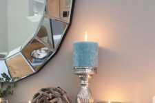 a glam coastal mantel with starfish and faux pearls, a driftwood ball and blue candles plus a shiny round mirror