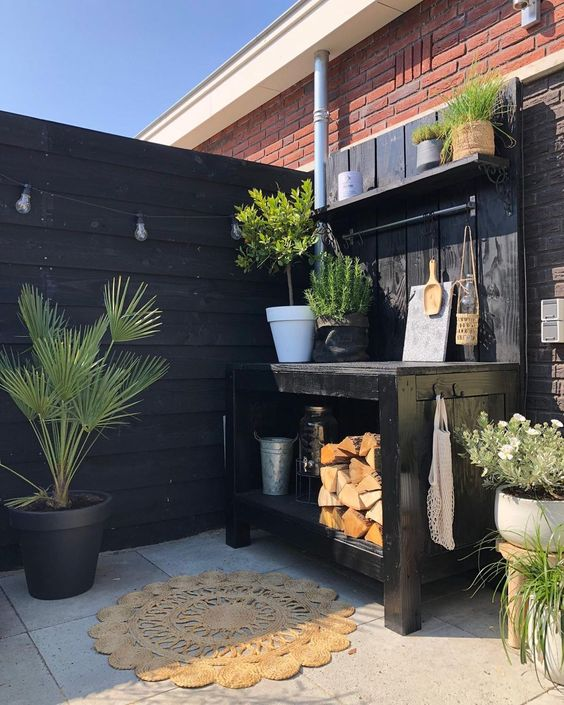 a gorgeous Scandinavian kitchen in black, with a small kitchen island with firewood, potted greenery and plants, a jute rug and a strign of lights