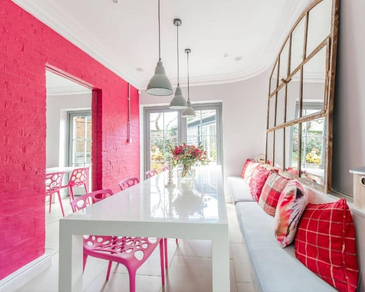 a gorgeous bubblegum pink dining room with a brick accent wall, hot pink chairs and printed pillows plus pendant lamps