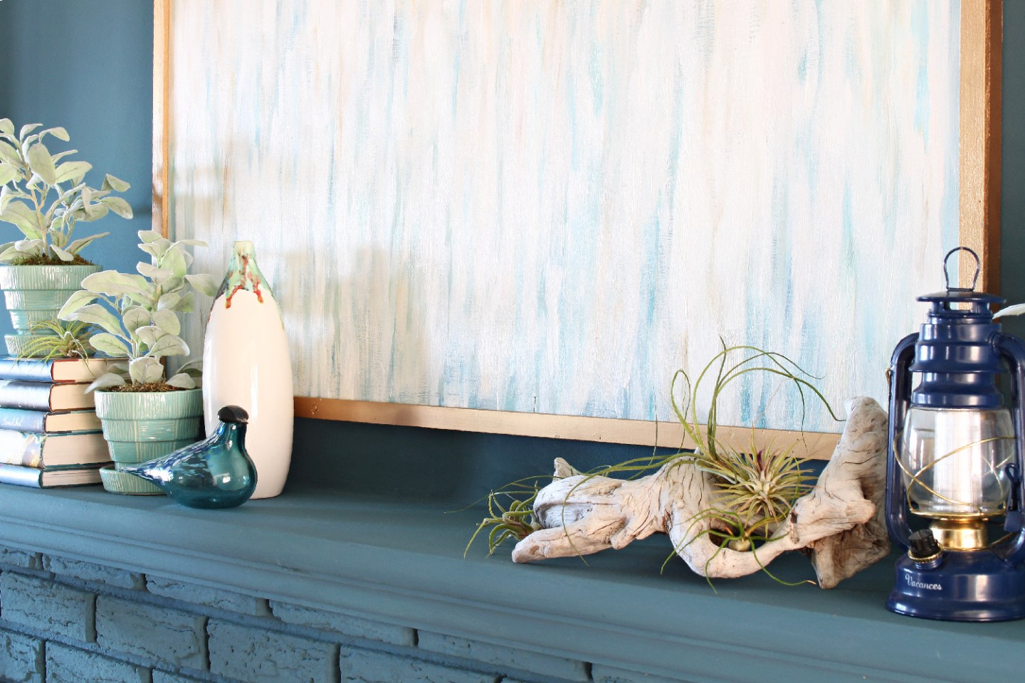 a gorgeous coastal mantel with a blue stack of books, a blue watercolor artwork, a navy candle lantern, driftwood and air plants