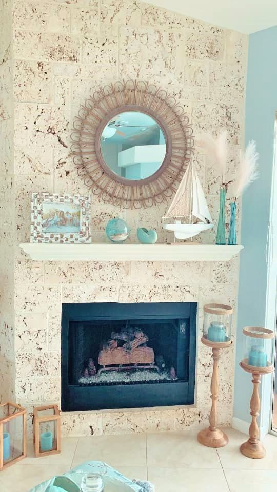 a gorgeous coastal mantel with a buoy, an aqua faux seashell, aqua vases with pampas grass, a boat and a family pic plus aqua candles around