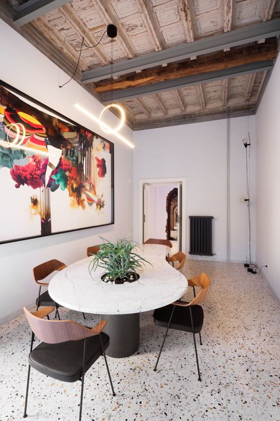 a gorgeous dining room with a bright terrazzo floor, a cool marble table and chic chairs, a statement artwork and a fantastic lamp