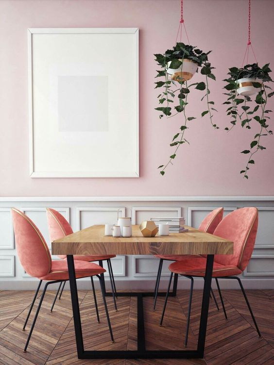 a gorgeous dining space with a pink and white panel wall, a wooden dining table, salmon pink chairs and suspended potted plants