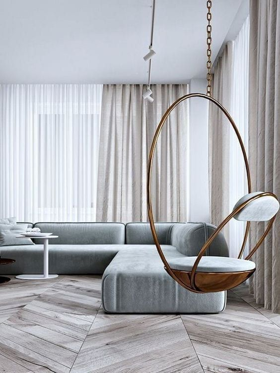 a gorgeous minimalist living room with a hardwood floor, a grey sectional, a pendant grey chair and neutral textiles