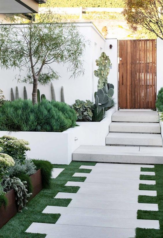 a jaw-dropping front yard with grass and stone tiles, with greenery, cacti, trees and succulents is a very welcoming space