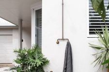 a little and lovely outdoor shower space with a grey wooden deck and a towel, potted plants and a tree stump as a stool