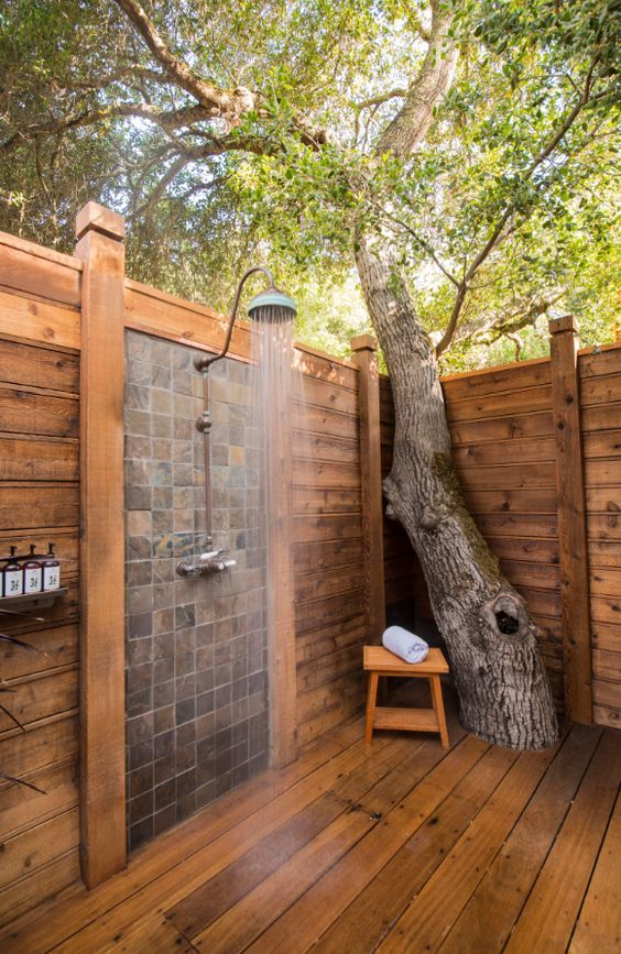 a lively outdoor shower space clad with planked wood, with a mosaic tile wall, a growing tree right here and a small stool