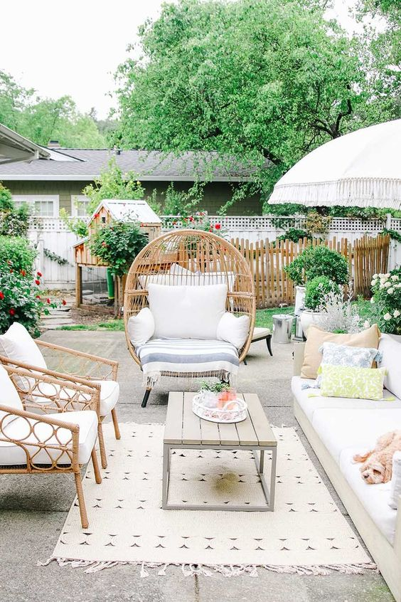 a lively summer terrace with rattan furniture, a comfy sofa, printed textiles, a low table and lots of greenery around