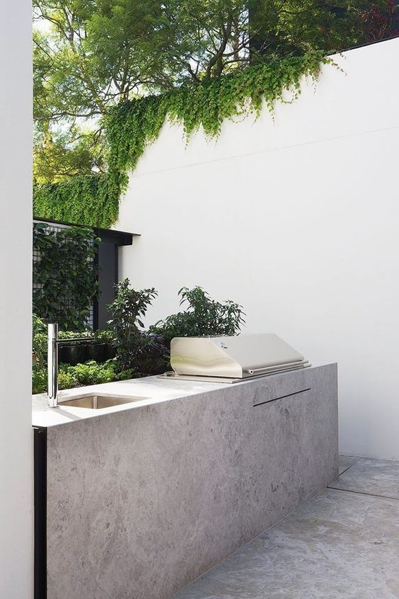 a lovely al fresco kitchen with a single cabinet of stone that matches the floor, a built-in grill and a sink