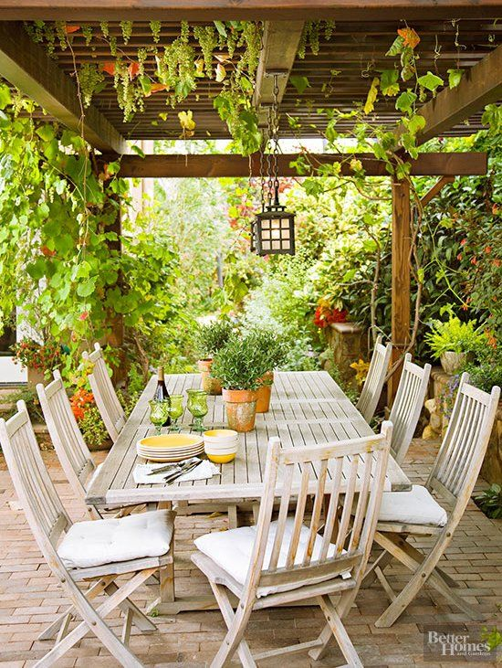 a lovely and welcoming outdoor dining space with a roof and much greenery hanging, a whitewashed wooden dining set plus pendant lamps
