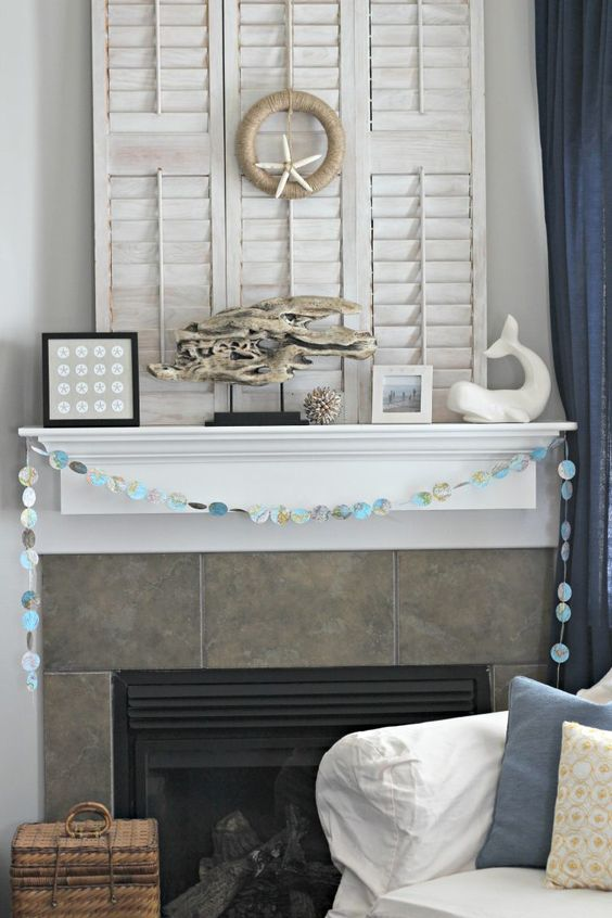a lovely coastal mantel with a seashell garland, a driftwood piece on a stand, a whale, some sea creatures for decor