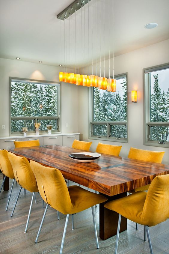 a lovely contemporary dining space with a long table, mustard chairs, a catchy pendant lamp and a view