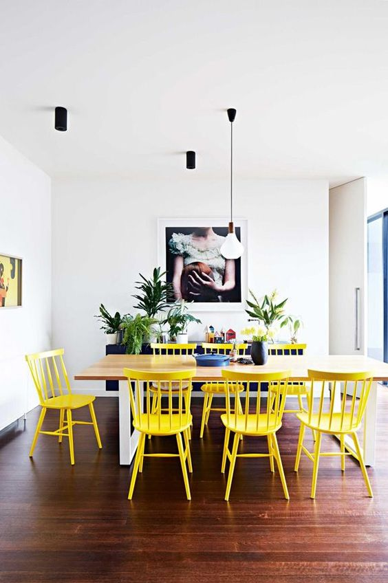 a lovely dining room with a navy sideboard, a wooden table, yellow chairs and a bench, lots of potted plants