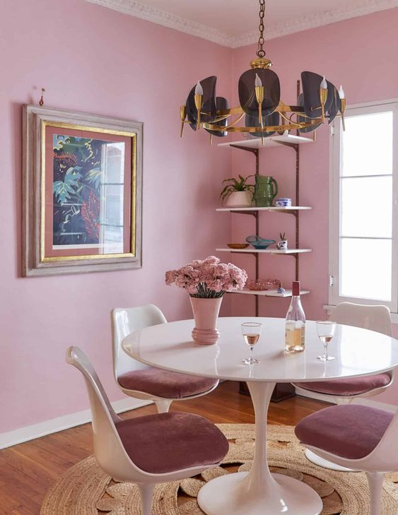 a lovely dining room with pink walls, an open shelving units, a round table and mauve chairs, a catchy black and gold chandelier