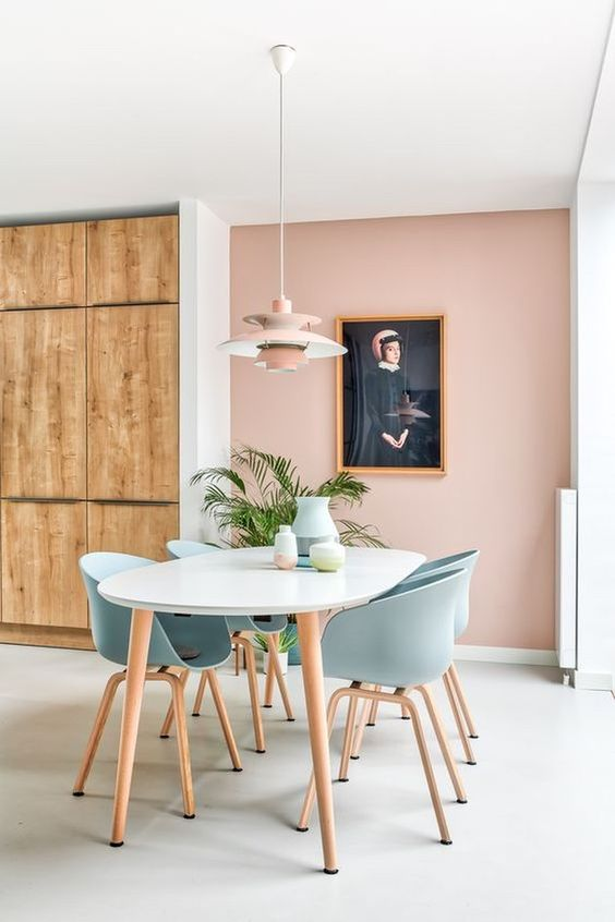 a lovely dining space with a blush accent wall, a white table and blue chairs, a pink pendant lamp and a statement potted plant