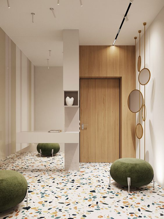 a lovely entryway with a bright terrazzo floor, green stools, cool pendant mirrors and a large mirror attached to the wall