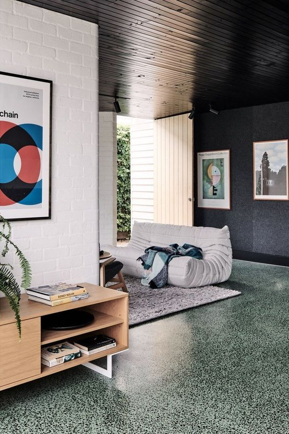 a lovely interior with black and white walls and a green terrazzo floor, a wooden ceiling and stylish furniture
