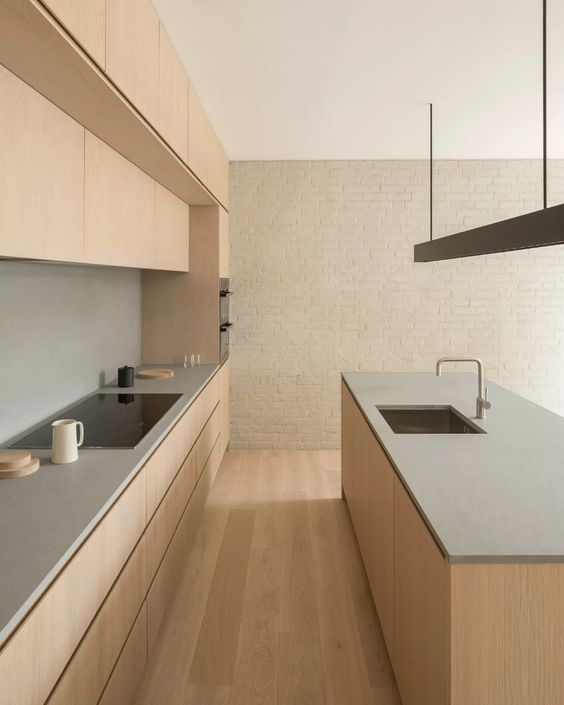 a lovely minimalist kitchen in warm tones, with sleek ligth stained cabinetry and a kitchen island, concrete countertops and a backsplash