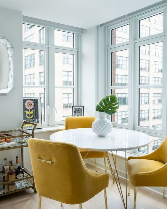 a lovely modern dining space with a view, a round hairpin table, yellow chairs, a gilded bar cart, a chic vase with a leaf