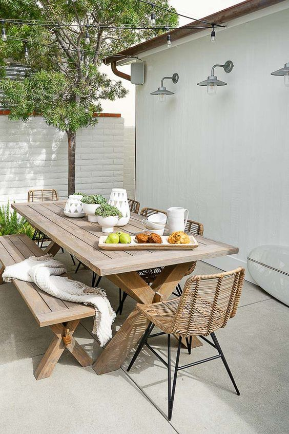 a lovely modern farmhouse dining space with a trestle table, a matching bench and some rattan chairs, greenery around and on the table