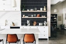 a lovely modern kitchen with a green terrazzo floor and a blush wall, white furniture and a black skinny tile backsplash