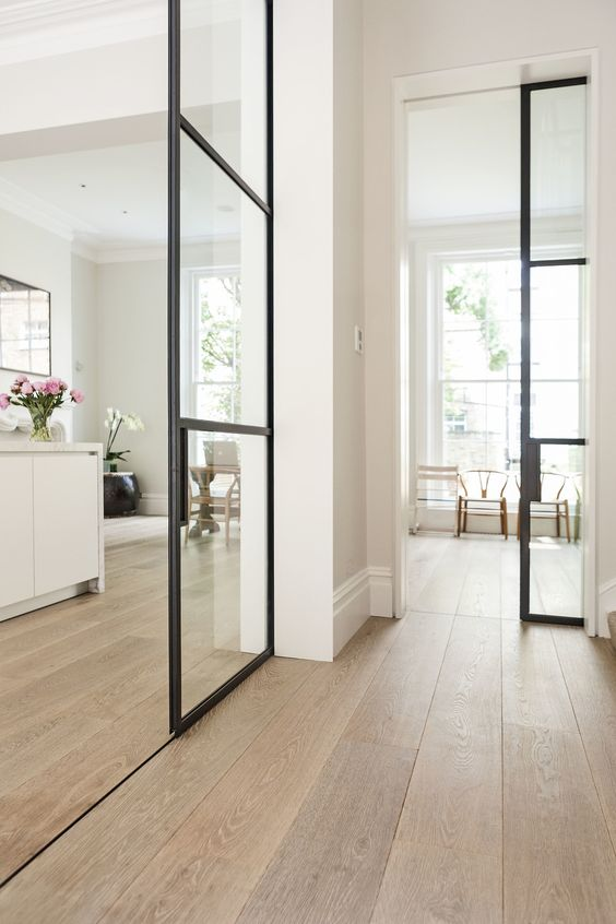 a lovely neutral contemporary space with light colored hardwood flooring, French sliding doors and chic furniture
