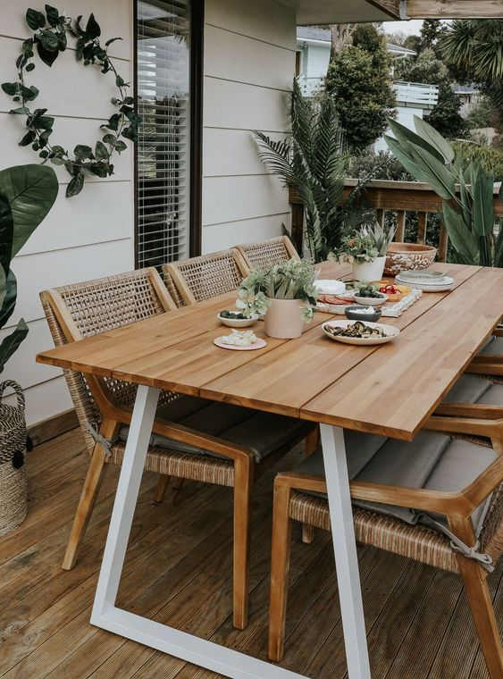 a lovely outdoor dining space with a simple table and woven chairs, with potted plants and a greenery wreath is welcoming