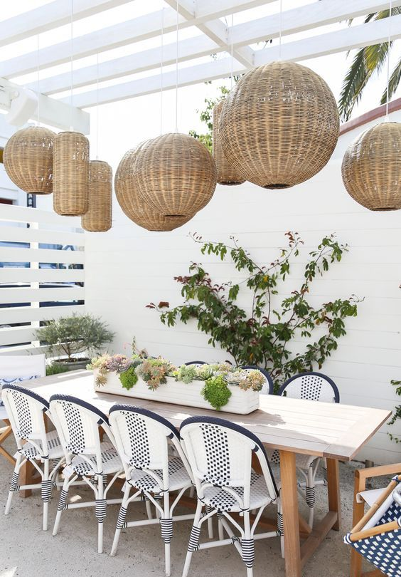 a lovely outdoor dining space with a whole cluster of pendant lamps, a long table and cool coastal chairs plus potted plants