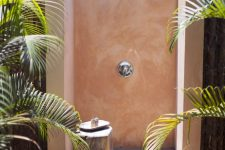 a lovely outdoor shower with a wooden deck, pink walls and a tree stump stool plus plants around is a cool space to refresh yourself