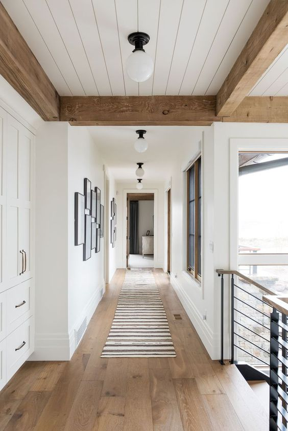 a lovely ranch space with white walls, a white planked ceiling, wooden beams and hardwood flooring is very inviting