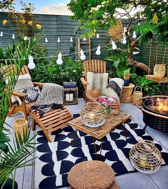 a lovely summer backyard with a tiled floor, wooden and jute furniture, a fire pit, potted greenery and string lights and candle lanterns