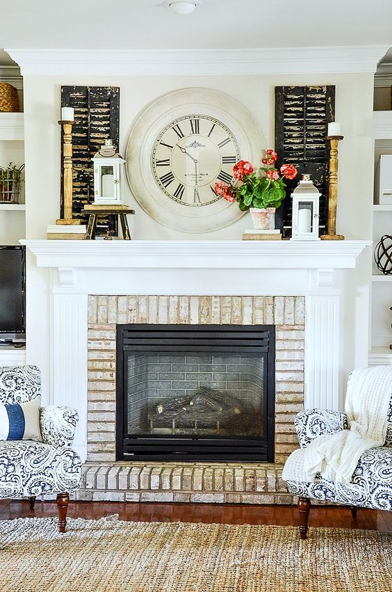 a lovely summer mantel with candles, candle lanterns, a vintage clock, shutters and a potted plant is a fun and cool idea