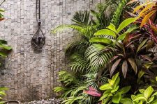 a lovely tropical outdoor shower with a stone wall and pallets and large stone tiles on the ground, lots of tropical plants and a bowl