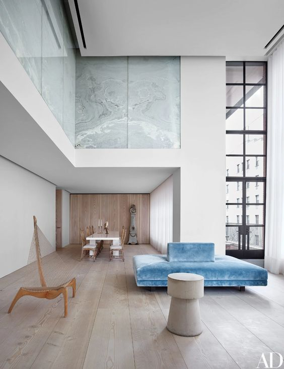 a luxurious minimalist space with stone panels, hardwood floors, double height windows, a blue sofa, a round side table is chic