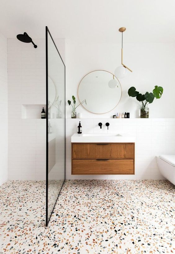 a mid-century modern bathroom with white walls and a bright terrazzo floor, a floating vanity and a round mirror, a pretty lamp and greenery