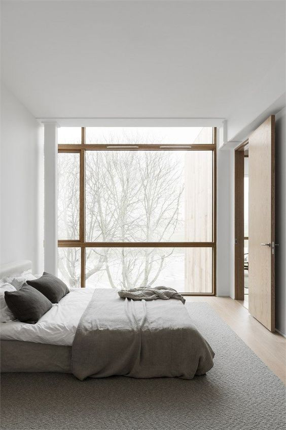 a minimalist bedroom with a glazed wall, an upholstered bed, neutral bedding and much negative space is chic
