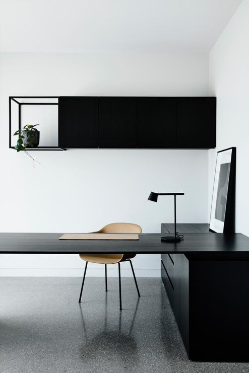 a minimalist home office with a black storage unit and shelf, a black desk and storage cabinets, a plywood chair and a table lamp